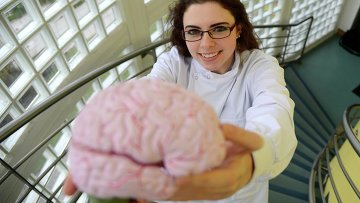 Ученый держит в руках мозг человека, страдавшего болезнью Альцгеймера