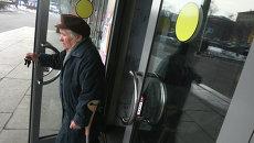 Пожилая женщина выходит из магазина. Архивное фото
