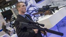 Сотрудник со снайперской крупнокалиберной бесшумной винтовкой Выхлоп на стенде компании Ростех на международной выставке Интерполитех-2015 в Москве