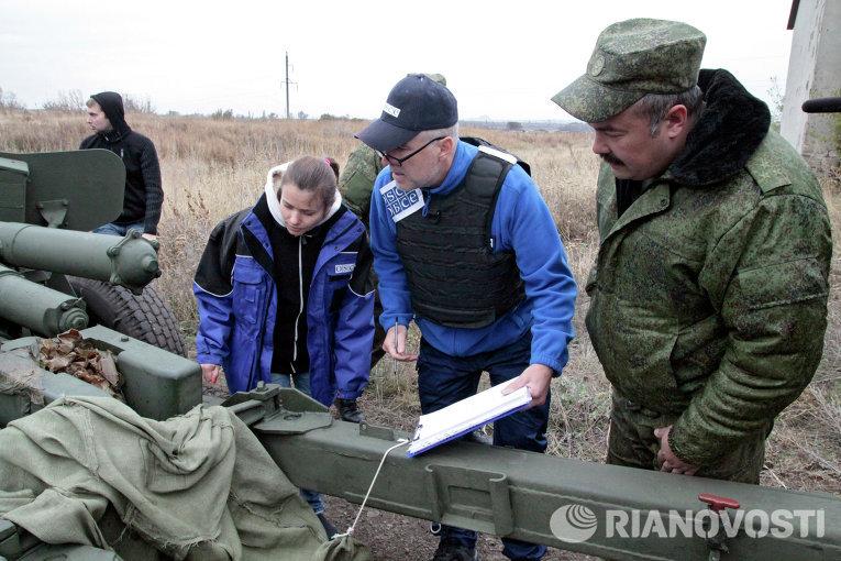 Представители ОБСЕ у военной техники, отведенной от линии соприкосновения ДНР, на специально подготовленной площадке в Донецкой области
