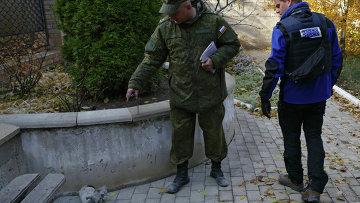 Сотрудники Совместного центра по контролю и координации режима прекращения огня в Донбассе и представители Специальной мониторинговой миссии ОБСЕ на месте обстрела