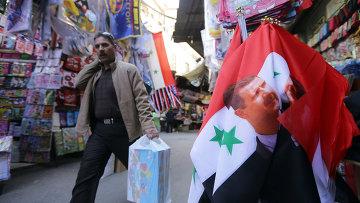 Флаг Сирии с изображением президента Сирии Башара Асада на рынке в Дамаске. Архивное фото