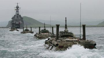 Колонна бронетранспортеров идет к большому десантному кораблю. Архивное фото