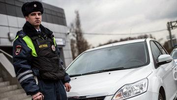 Сотрудник ГИБДД рядом с автомобилем без специальных знаков и проблескового маячка во время рейда скрытых патрулей ДПС в Москве
