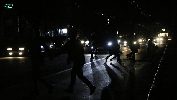 Жители Симферополя переходят автодорогу в свете фар автомобилей