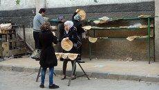 Горожане раскладывают горячий хлеб в Старом городе Дамаска