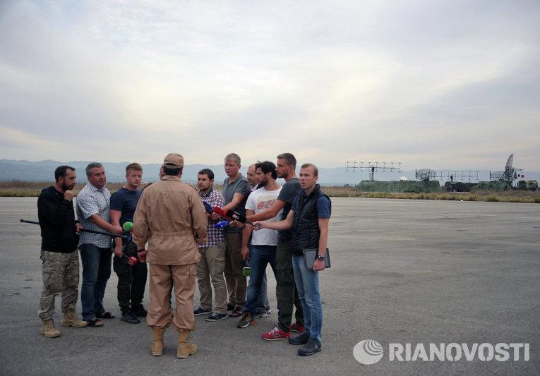 Спасенный летчик Су-24 Военно-космических сил России капитан Константин Мурахтин (в центре) отвечает на вопросы журналистов на авиабазе Хмеймим