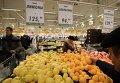 """Покупатели у прилавка с лимонами и апельсинами из Турции в торговом зале гипермаркета """"Глобус"""""""
