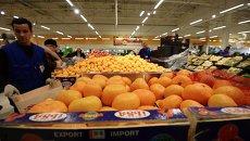 Продавец у прилавка с мандаринами в торговом зале гипермаркета Глобус. Архивное фото