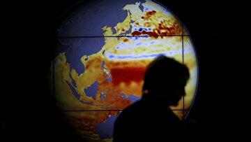 Женщина проходит мимо карты на конференции по климату, 11 декабря 2015 года