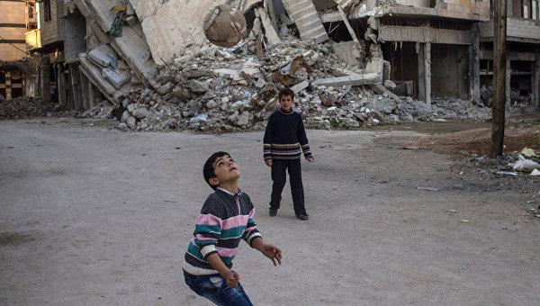 Дети играют в мяч в разрушенном районе Хомса аль Хамидия. Архивное фото