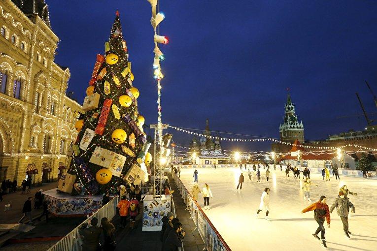 Люди катаются возле елки на Красной площади в Москве
