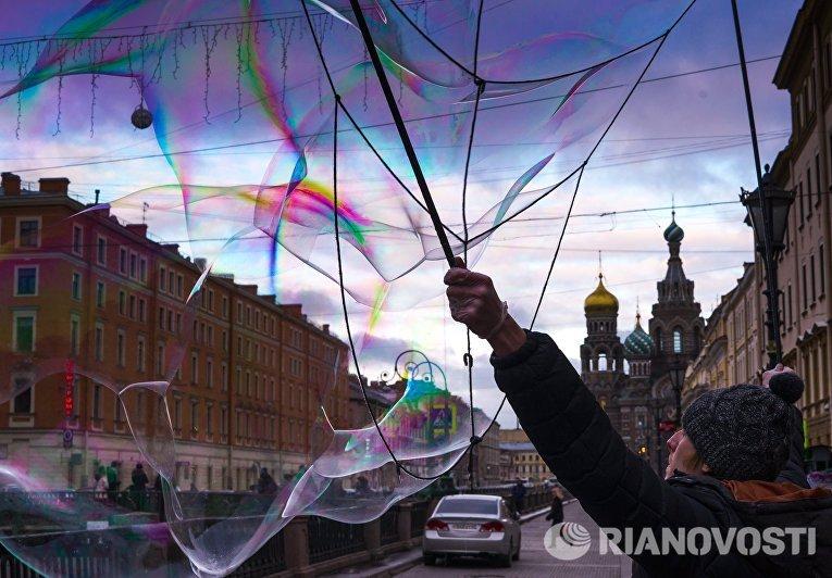Уличный артист надувает мыльные пузыри на набережной канала Грибоедова в Санкт-Петербурге