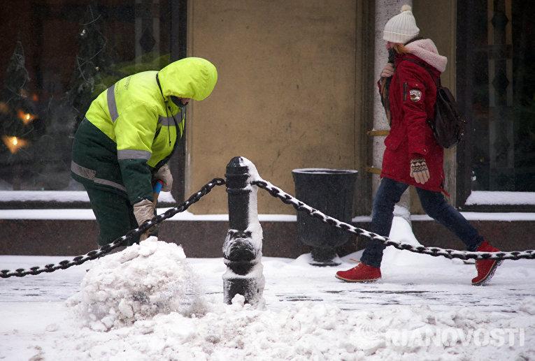 Мужчина убирает снег на Невском проспекте в Санкт-Петербурге
