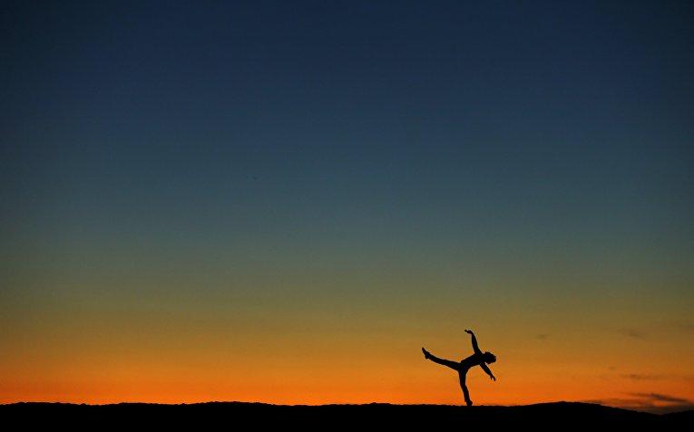 Мужчина танцует на фоне заката в Калифорнии, США