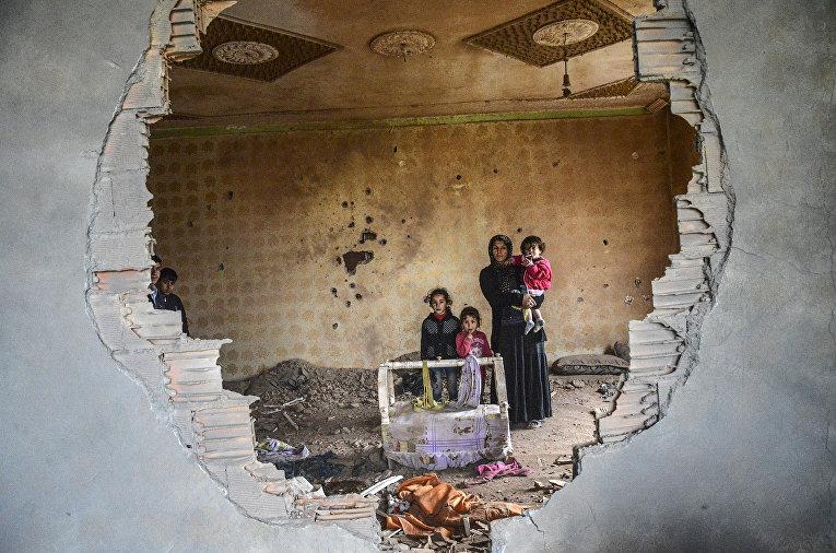 Женщина и дети в разрушенном доме в Курдском городе Силопи на юго-востоке Турции, недалеко от границы с Ираком. 19 января 2016 год