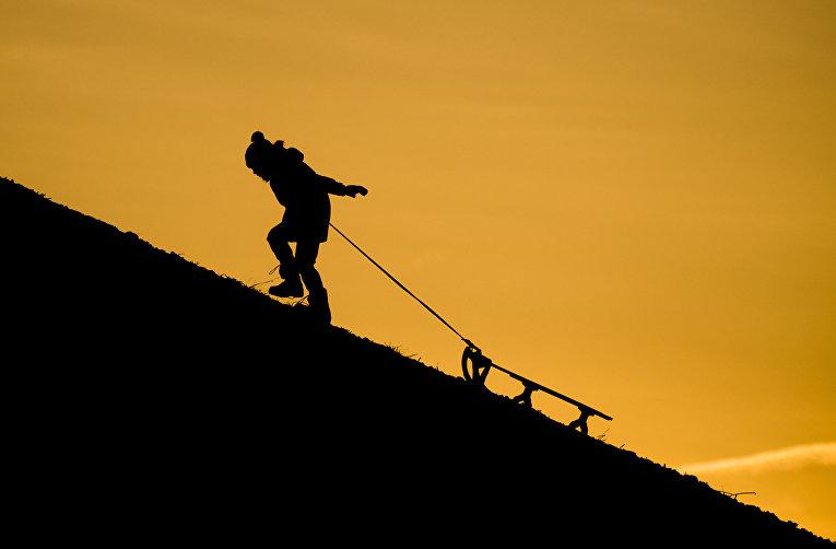 Ребенок тащит санки на холме Кронсберг, Германия