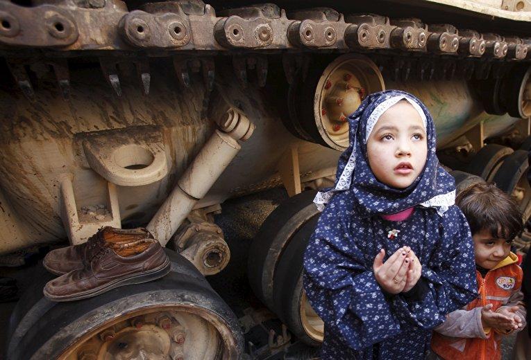 Девушка молится около танка на площади Тахрир в Каире. 18 февраля 2011 года
