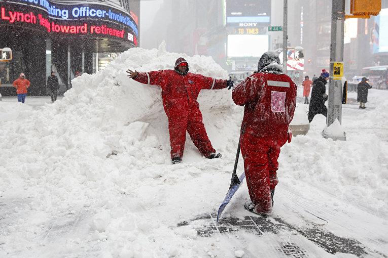 Сотрудники коммунальной службы Нью-Йорка фотографируются на фоне сугробов после снегопада. Январь 2016