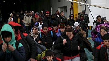 Мигранты, прибывшие на пароме в порт недалеко от Афин, Греция. 23 января 2016