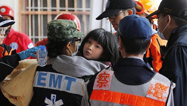 Спасатели помогают ребенку, пострдавшему во время землетрясения на Тайване, 6 февраля 2016