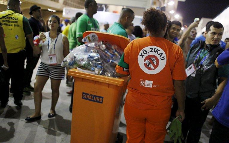 Работник из клининговой компании собирает мусор во время карнавального шествия в Самбодром в Рио-де-Жанейро