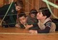 Ребята преодолевают лазерный лабиринт из натянутых нитей