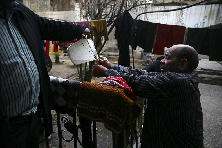 Инвалид Шахрур моет руки возле своего дома, Ирбин, Сирия