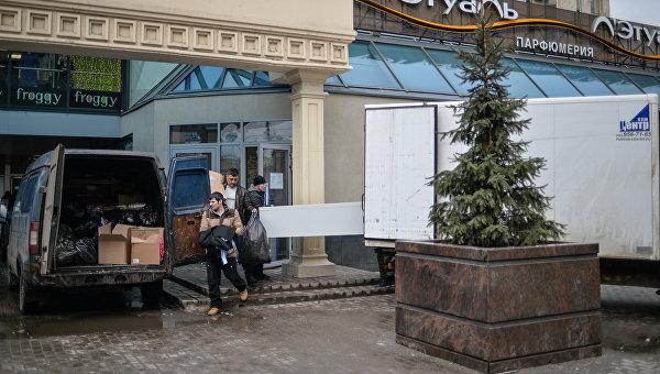 Рабочие выносят имущество из торгового центре Пирамида на Пушкинской площади Москвы