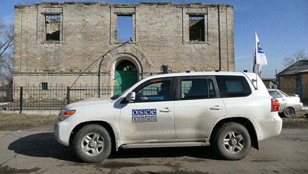 Автомобиль ОБСЕ у разрушенного дома в поселке Зайцево в Донецкой области. Архивное фото
