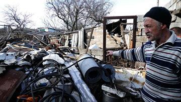 Местный житель у разрушенного дома в поселке Зайцево в Донецкой области. Архивное фото