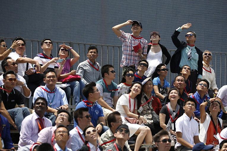 Зрители наблюдают за выступлением пилотажной группы Black Eagles из Южной Кореи на авиашоу Singapore Airshow в Сингапуре