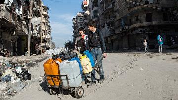 Местные жители с емкостями для воды в жилом квартале города Алеппо, Сирия