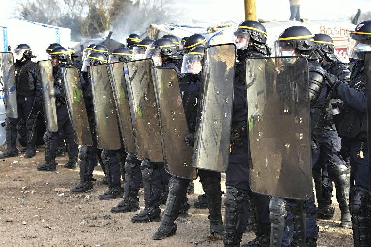 Сотрудники полиции в лагере мигрантов Джунгли возле Кале, Франция. 29 февраля 2016