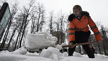 Работница ЖКХ убирает снег на одной из улиц Москвы