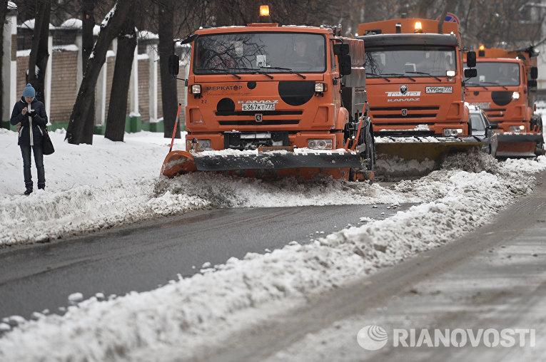 Специальные машины управления жилищно-коммунального хозяйства (ЖКХ) убирают снег на одной из улиц Москвы