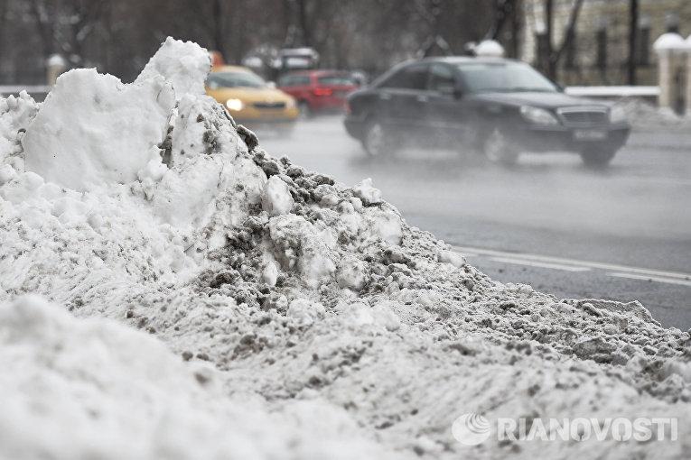 Сугробы снега на одной из улиц Москвы, образовавшиеся после сильного снегопада