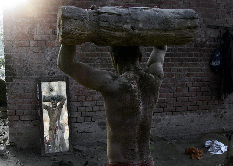 Рестлер смотрит на себя в зеркало во время тренировки в Лахоре, Пакистан. 2 марта 2016
