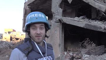Корреспондент RT Уильям Уайтман на фоне разрушенного здания в городе Джизре