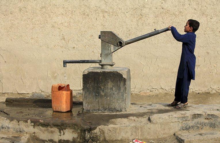 Ребенок в ручного насоса. Пешавар, Пакистан