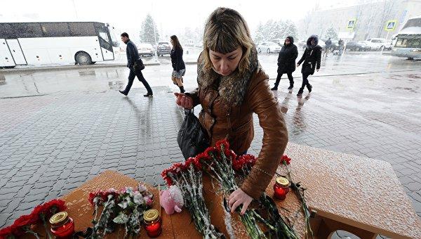Женщина возлагает цветы у аэропорта Ростова-на-Дону, где при посадке разбился пассажирский самолет Boeing-737-800