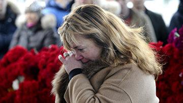 Женщина возлагает цветы у аэропорта Ростова-на-Дону, где при посадке разбился пассажирский самолет Boeing-737-800. Архивное фото