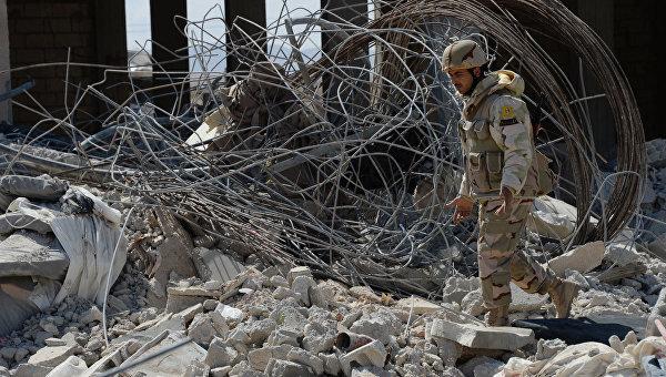 Боец отряда народного ополчения Соколы пустыни у разбитого здания в результате боев в 10-ти км к западу от Пальмиры