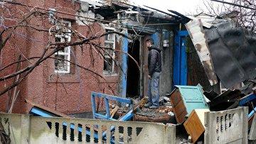 Мужчина у дома, поврежденного в результате обстрела украинскими силовиками, в Макеевке. Архивное фото
