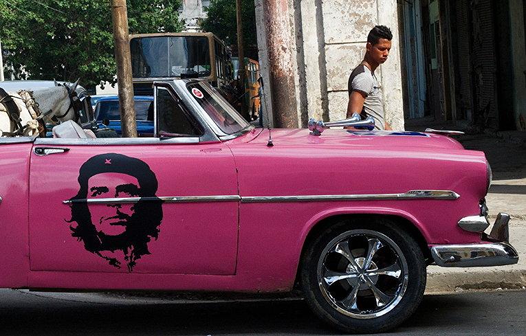 Американский классический автомобиль с портретом Че Гевары на улице Гаваны, Куба