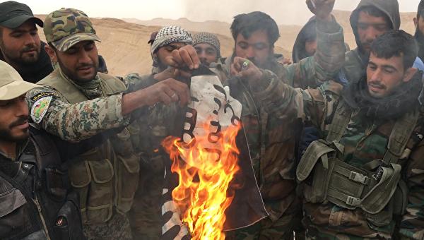 Сирийские солдаты сжигают флаг террористической группировки Исламское государство (запрещенная в РФ). Архивное фото