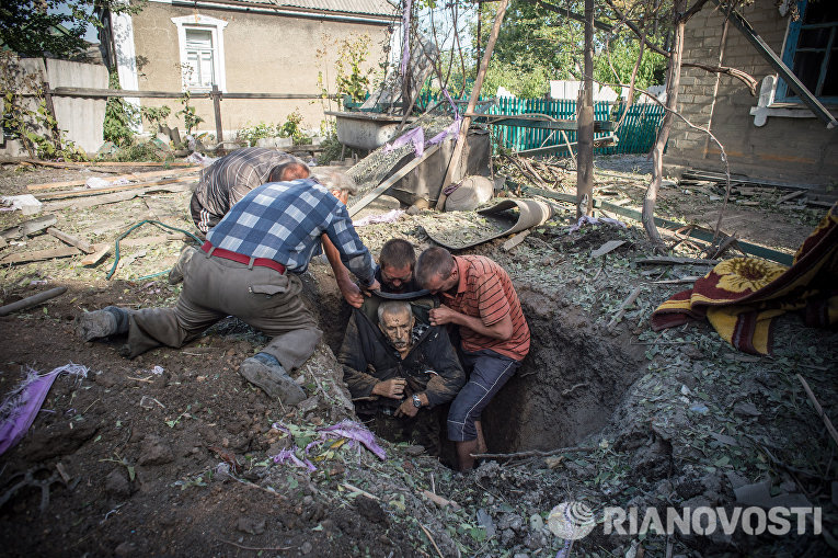 Местные жители достают из укрытия тело погибшего в результате обстрела поселка Александровка в Донецкой области