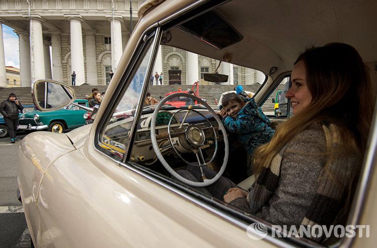 Девушка в автомобиле ГАЗ-М-21 на выставке ретро-автомобилей в Санкт-Петербурге