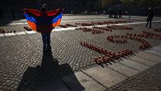 Демнотстрант держит флаг Армении перед Рейхстагом во время проходящих там слушаний о резне армян турками-османами в 1915 году. Архивное фото