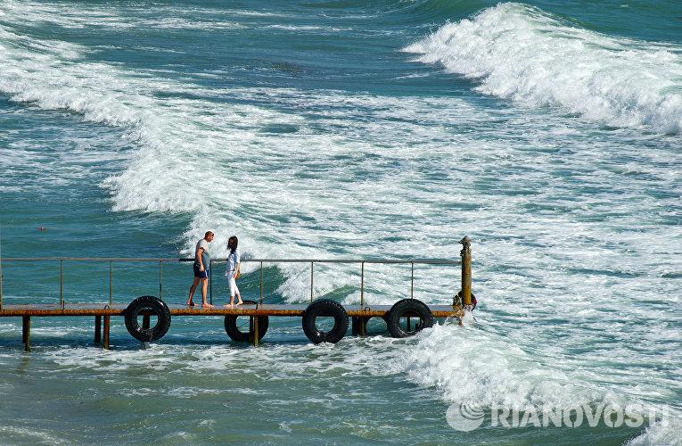 Отдыхающие на берегу Черного моря в поселке Орджоникидзе в Крыму